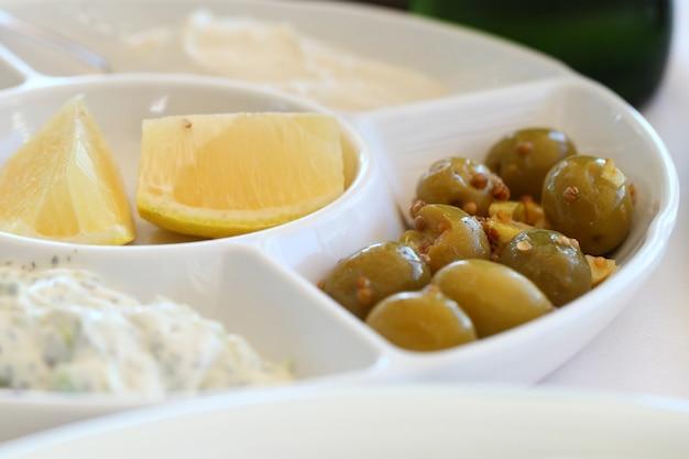 Зеленые оливки, лимон и йогурт, цацики в тарелке, закуска к еде.
