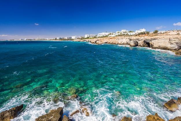Скалистый берег, чистая бирюзовая морская вода и голубое небо в айя-напе, кипр.