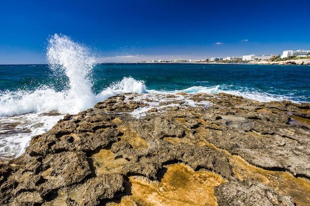 岩の多い海岸、澄んだ青緑色の海水、波は岩の上の水しぶき、青い空で壊れます。アヤナパ、キプロス。