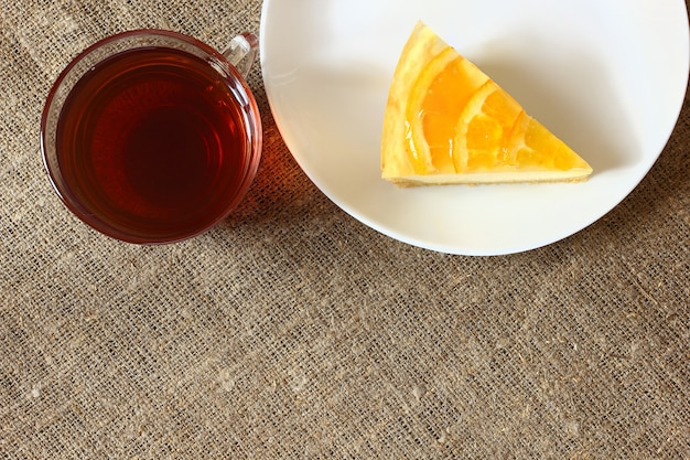 白い皿にオレンジとチーズケーキ、黄麻布のテーブルクロスにお茶とガラスのマグカップ。上面図。