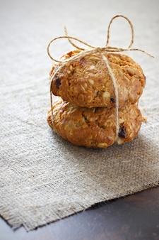 レーズンとフィラーが入ったオートミールクッキーは、粗い灰色のテーブルクロスと暗い卓上に弓でロープで縛られています。