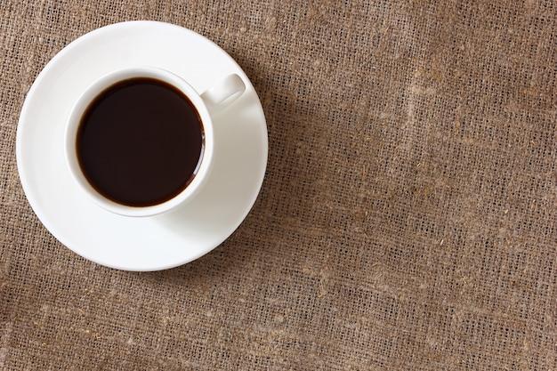 黄麻布のテーブルクロスにマグカップとソーサーでコーヒー。上面図。