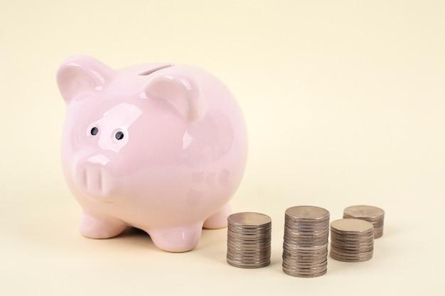 ピンクの貯金箱と黄色の背景上のコイン