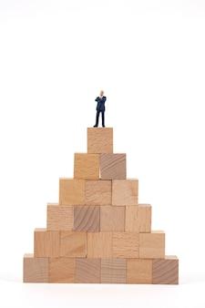 木製のブロックの上に立ってミニチュア実業家