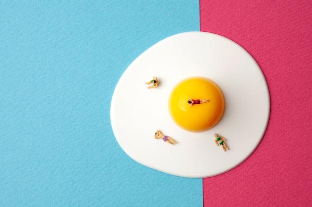 Миниатюрные люди на яйце с синей и розовой поверхностью