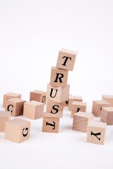 Слово доверия написано в башне деревянных кубиков