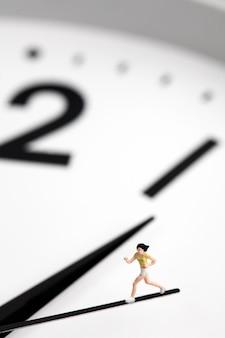 秒針時計で実行されているミニチュアの女の子