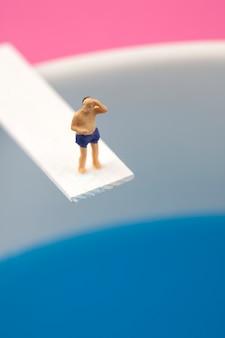 ダイビングボードに立っているミニチュア男
