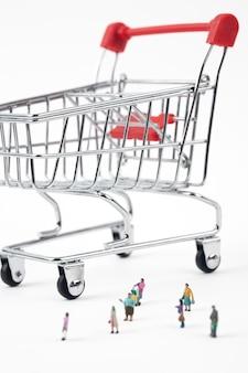 ショッピングカートとミニチュアの買い物客