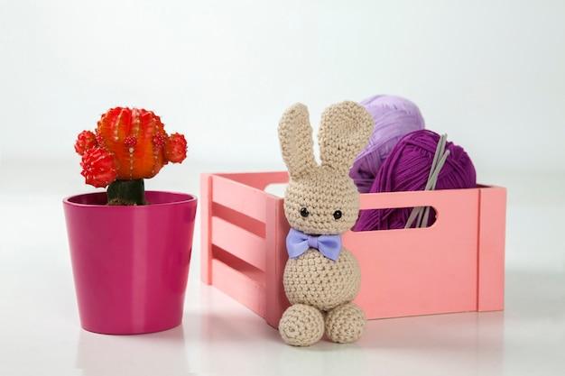 Кролик амигуруми с черными глазами и галстуком-бабочкой, кактусом, шерстяной коробкой и крючками