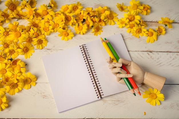 Тетрадь из белой бумаги среди цветов, карандаши и блокнот с эластичной застежкой
