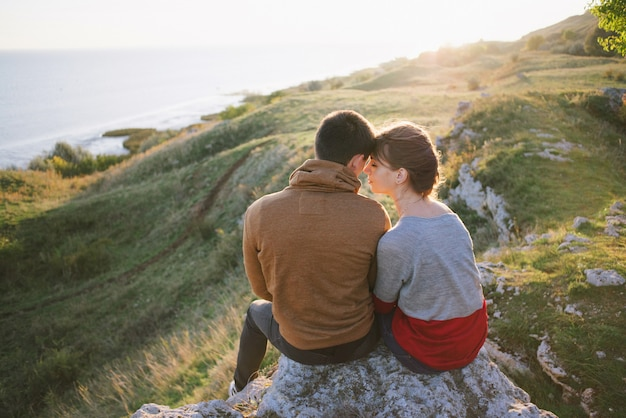 Молодые влюбленные на закате в горах