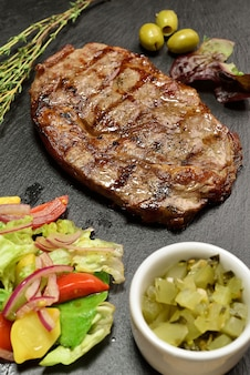 スレートプレートにサラダと牛肉ステーキ