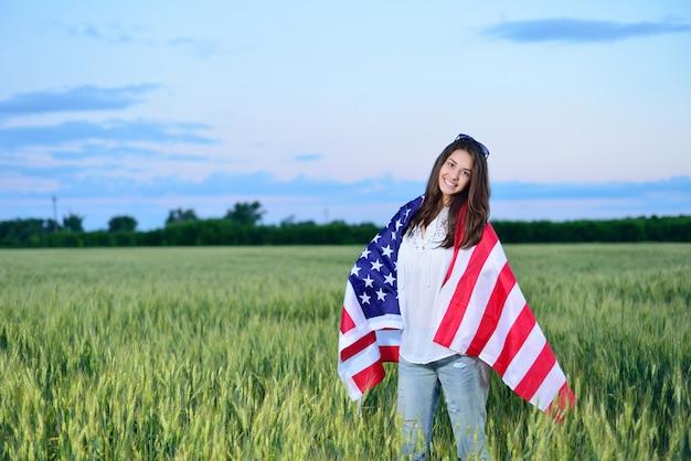 彼女の肩にアメリカの国旗と笑顔の幸せな女の子