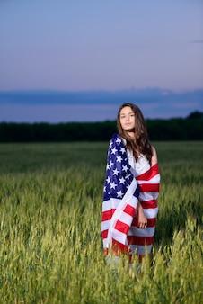 彼女の肩にアメリカの国旗を持つ少女