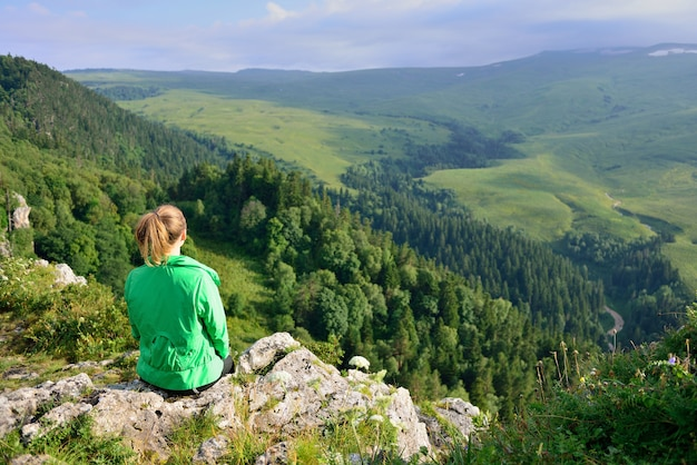 崖の端に座っている女の子