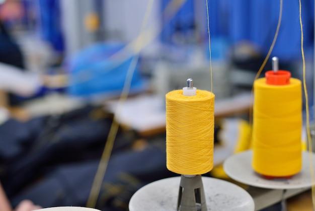 Катушки ниток в швейном оборудовании. концепция швейного производства.