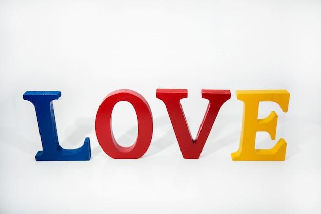 Любовь цветные деревянные буквы на белом фоне.