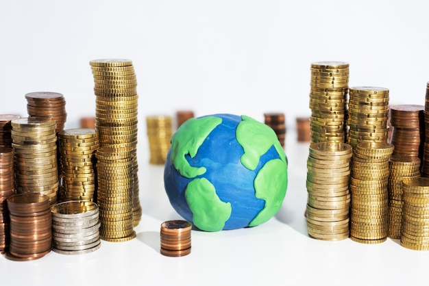地球モデルと白いテーブルの上のコインがたくさん