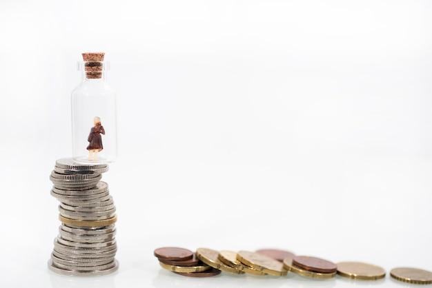 Маленькая женщина в пробирке на монетах. абстрактное фото финансового кризиса.