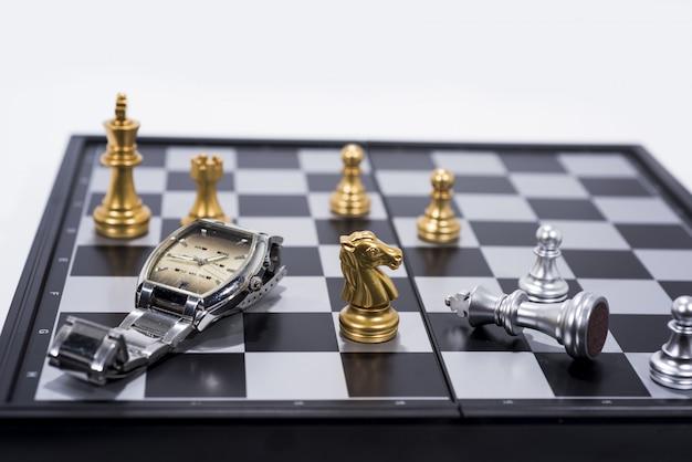 Шахматная доска на белых, золотых и серебряных фигурках с ручными часами