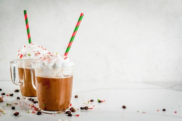 自家製ペパーミントモカ、白い大理石のテーブルの上にキャンディー、ホイップクリーム、ミントシロップとクリスマスコーヒーを飲む
