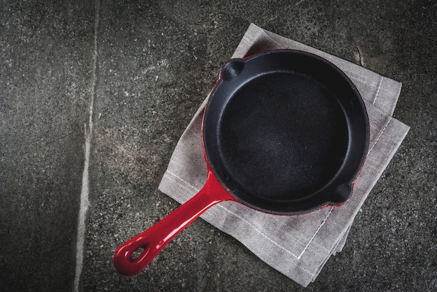 料理の背景。黒い石のテーブルにタオルで空の赤い鋳鉄フライパン