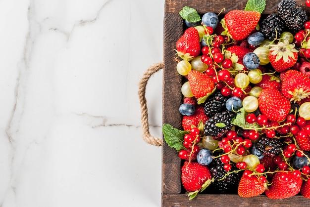 Летние фрукты и ягоды. виды сырых органических фермерских ягод малина ежевика черника клубника красная смородина крыжовник. стол из белого мрамора, деревянный поднос. вид сверху