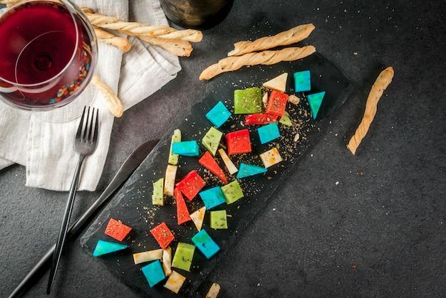 Модная современная еда. разноцветный красочный голландский сыр голубая лаванда, красный (острый перец), зеленый (базилик), классический желтый сыр. с хлебными палочками, бокалом, черным столом. вид сверху