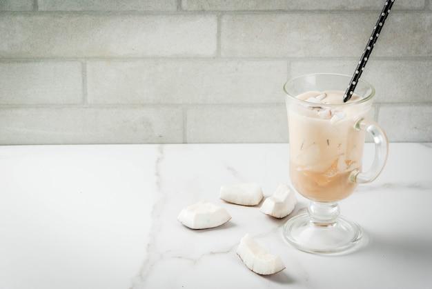 Веганская еда. освежающие летние коктейли. напитки. кокосовое латте смузи с кофе, кокосовым кремом, молоком, кусочками кокоса. на белом мраморном кухонном столе.