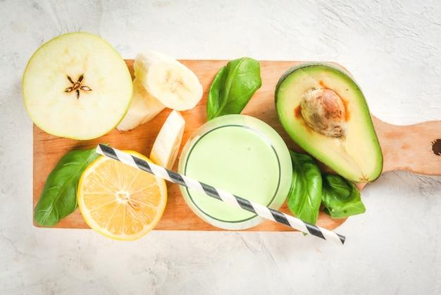 健康食品。食事の朝食または軽食。ヨーグルト、アボカド、バナナ、リンゴ、ほうれん草、レモンのグリーンスムージー。食材を使った白いコンクリートの石のテーブルの上。上面図