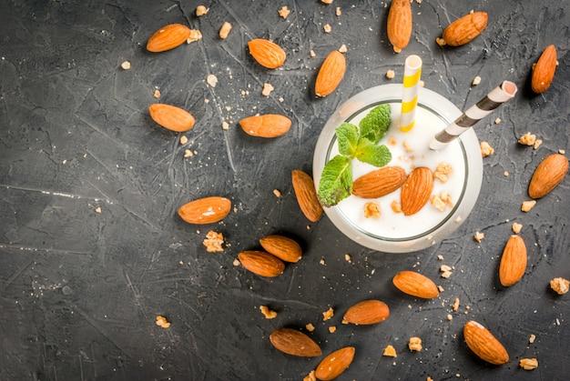 健康食品。食事の朝食または軽食。ヨーグルト、バナナ、アーモンドナッツから作られた白いスムージー。ミントで飾られました。食材、縞模様のストローのある暗いコンクリートのテーブル。上面図
