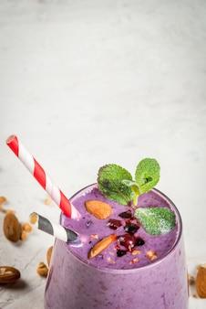 Здоровая пища. диетический завтрак, закуски. ягодные смузи с мюсли, черной смородиной, черникой и орехами, миндалем, украшенные мятой. на белом бетонном столе с ингредиентами,