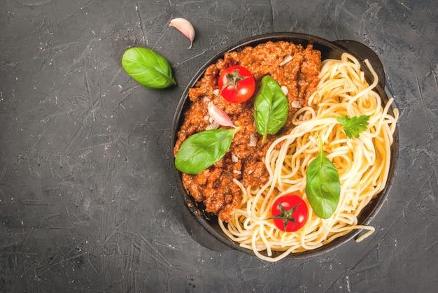 Ингредиенты итальянской кухни. продукты для приготовления пасты болоньезе, процесс приготовления. спагетти, соус болоньезе, базилик, чеснок, помидор, пармезан в кастрюле.