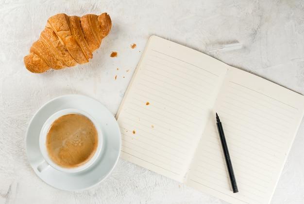 コーヒー、クロワッサン、メモ帳