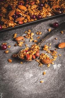冬、秋の朝食のアイデア。感謝祭、。ナッツサーモンド、ピーナッツ、ヘーゼルナッツ、クランベリーと自家製の新鮮な調理された蜂蜜グラノーラ。灰色のコンクリートテーブルの上に、