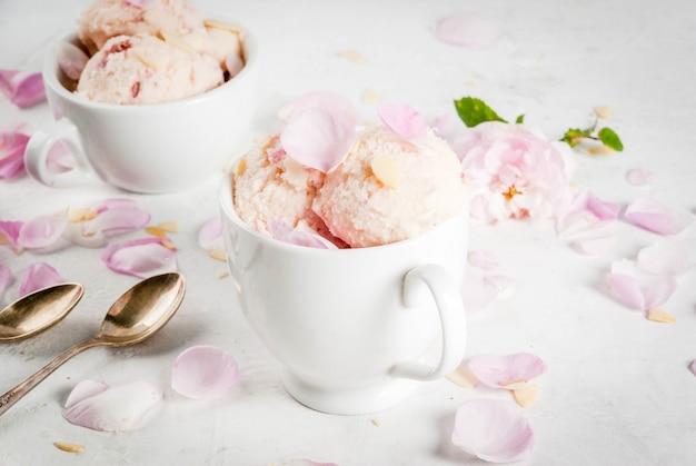 夏のさわやかなデザート。ビーガンダイエット食品。バラの花びらとアーモンドのスライス、白いサービングボウル、白いコンクリートのテーブルの上にアイスクリーム。