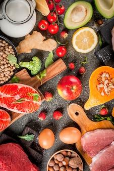 健康的なダイエット 。有機食材、スーパーフード:牛肉と豚肉、鶏肉の切り身、サケ、魚、豆、ナッツ、牛乳、卵、果物、野菜。黒い石のテーブル、トップビュー