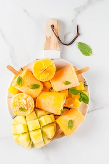 アイスクリーム、アイスキャンディー。オーガニック食材、デザート。冷凍マンゴースムージー、ミントの葉、新鮮なマンゴーフルーツ、プレート、白い大理石のテーブルの上に。上面図