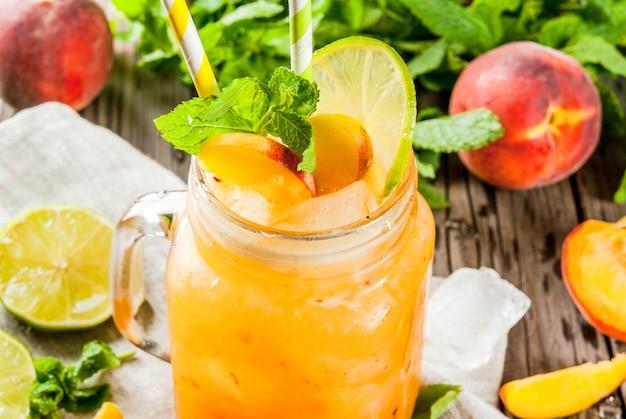 Летние напитки, коктейли. веганская еда. персиковые смузи, сок или лимонад. в банке с масоном, с лаймом, рубленым льдом и листьями мяты. на старый деревенский деревянный столик с ингредиентами.