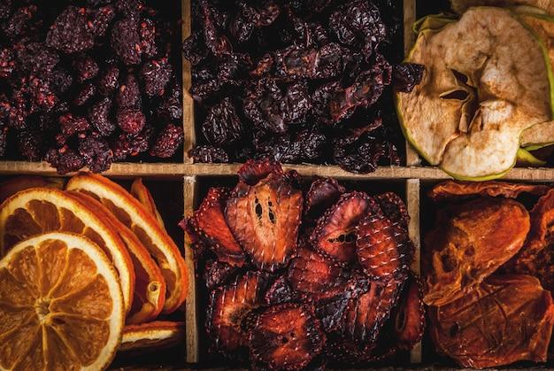 Домашние сушеные ягоды и фрукты, урожай на зиму: абрикосы, яблоки, клубника, малина, вишня, апельсины. в старом деревянном ящике, на черном каменном столе