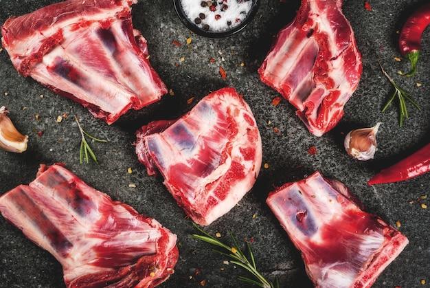 生の新鮮な肉、生の子羊または牛カルビ、唐辛子、ニンニク、暗い石の背景にスパイス