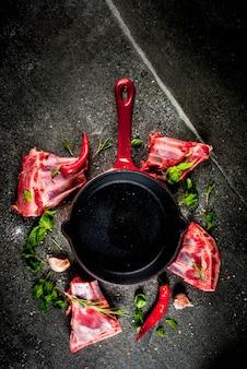生の新鮮な肉、生の子羊または牛肉のリブ、唐辛子、ニンニク、フライパンのフライパンとスパイスの暗い石の背景