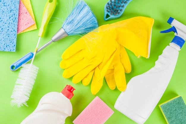 用品、ハウスクリーニング製品の山と春の大掃除のコンセプト。緑の背景の上面に家事のコンセプト
