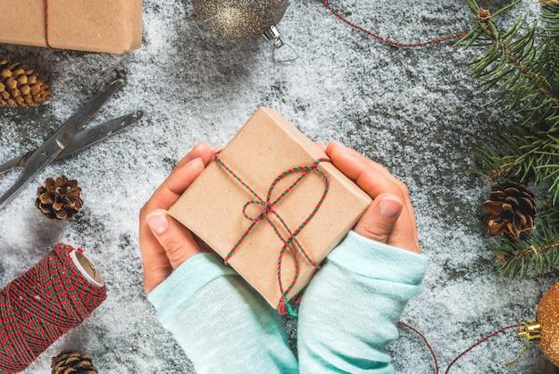 クリスマスのコンセプト、テーブルの背景に雪、クリスマスツリーの枝、女の子の手で保持ギフトまたはプレゼント、松ぼっくりや装飾