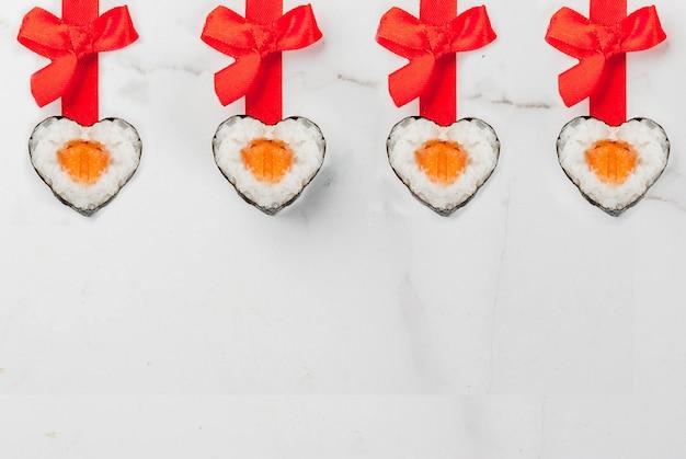 本物の寿司は、赤いリボンと弓でハートの形でバレンタインの日に設定します。白い大理石の背景コピースペーストップビュー