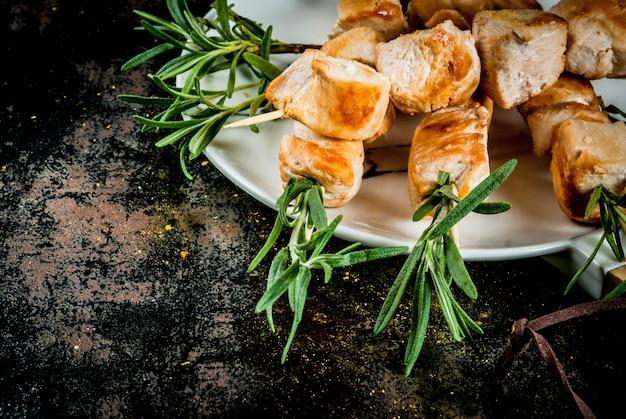 グリル、バーベキュー肉。ローズマリーと鶏の串焼き。黒さびた金属、トップビュー