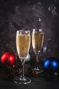 Сухое шампанское в бокалах, разноцветные елочные шары, сосновые шишки, новогодний натюрморт на темном камне, селективный фокус