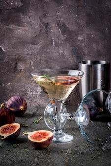 Рецепты напитков осенью и зимой, коктейль мартини с инжиром, тимьяном и медом, на черном каменном столе,
