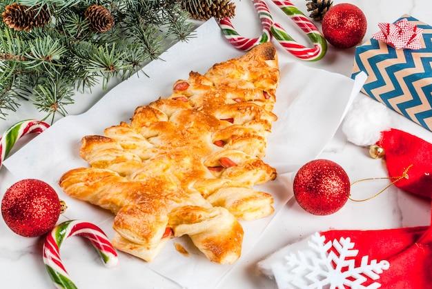 クリスマスパーティーのスナック。クリスマスツリーの形でパイ生地からピザを閉じた。白い大理石のテーブルの上。クリスマスの飾り付き